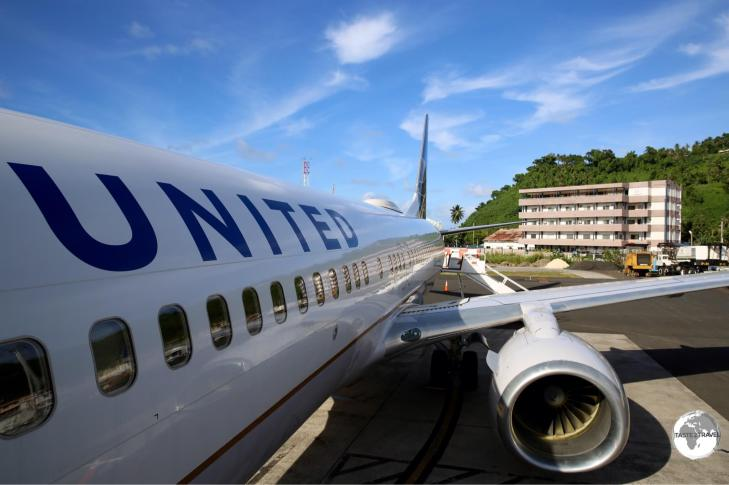 United Airlines' UA154 on the runway at Chuuk International Airport with my hotel, Hotel Level 5, visible in the background.