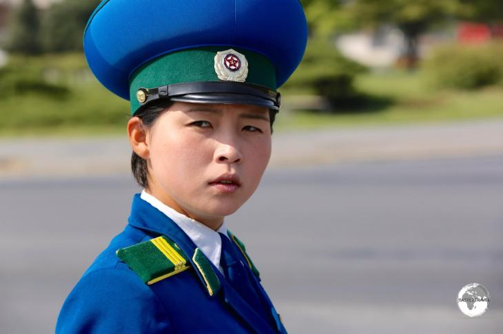 North Korea Travel Guide: Traffic policewoman in Pyongyang. Most drivers are male so the state employs young, attractive female officers as they believe the male drivers pay them more respect.