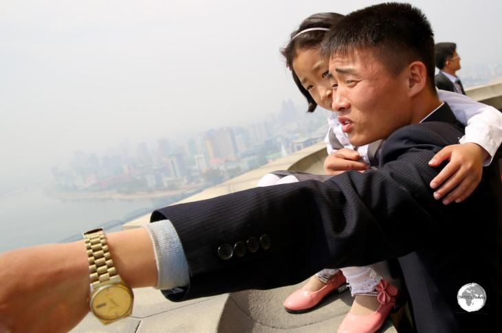 A North Korean family enjoying the panoramic views of Pyongyang from the top of the Juche Tower.