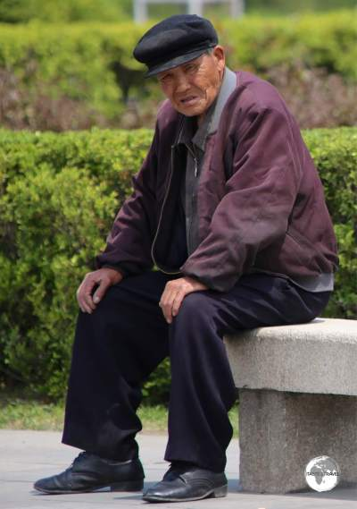 An old man relaxing at the <i>Monument to Party Founding</i> in Pyongyang.