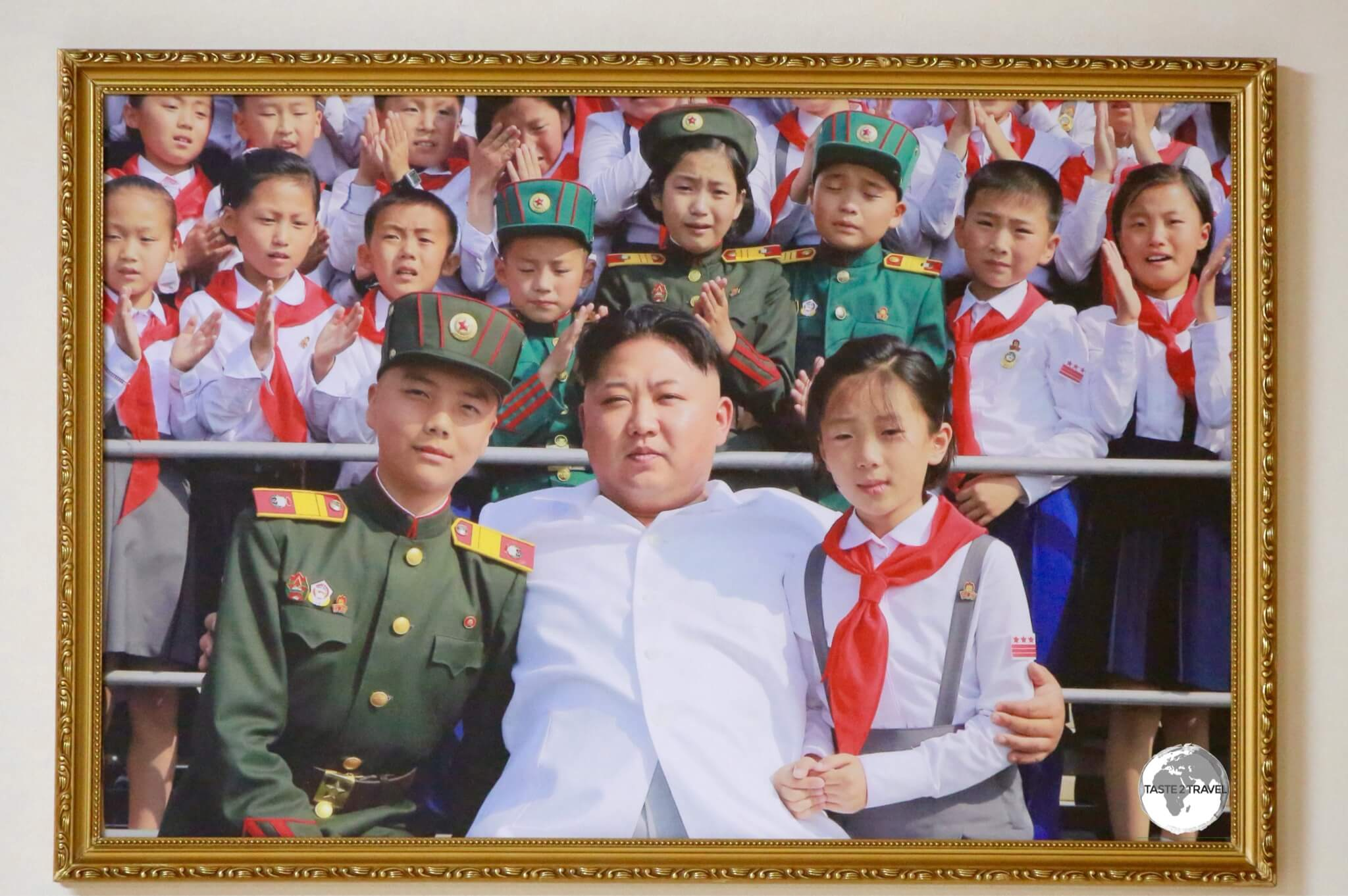 Although current leader Kim Jong-un's image is not displayed publicly, there are photos and paintings of him featured in galleries. Notice the children behind him are crying tears of joy.