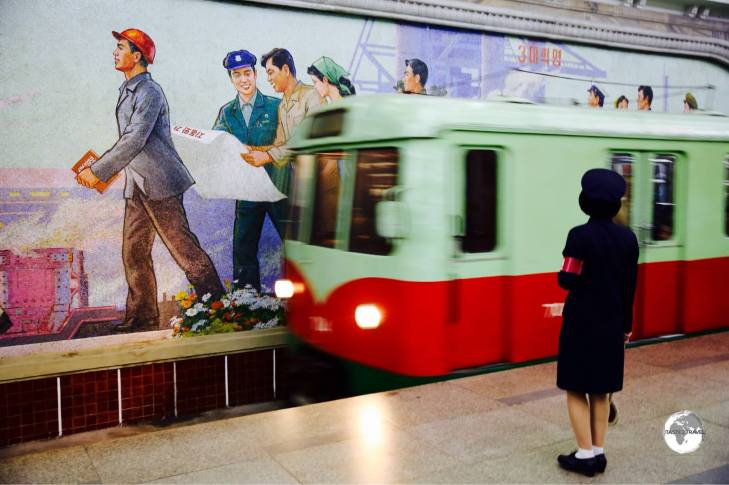 A train arrives at Puhung station, passing in front of a mosaic propaganda mural.
