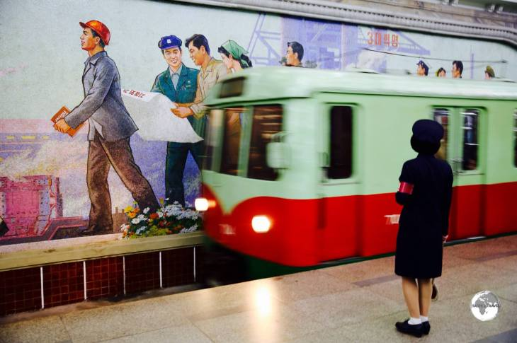 A train arrives at Puhung station on the Pyongyang metro, passing in front of a mosaic propaganda mural.