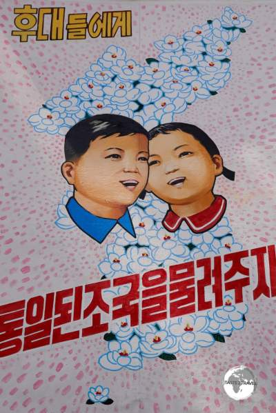 A propaganda billboard at the DMZ depicts a reunified North and South Korea. The Korea's are often depicted as brother and sister in North Korean propaganda.