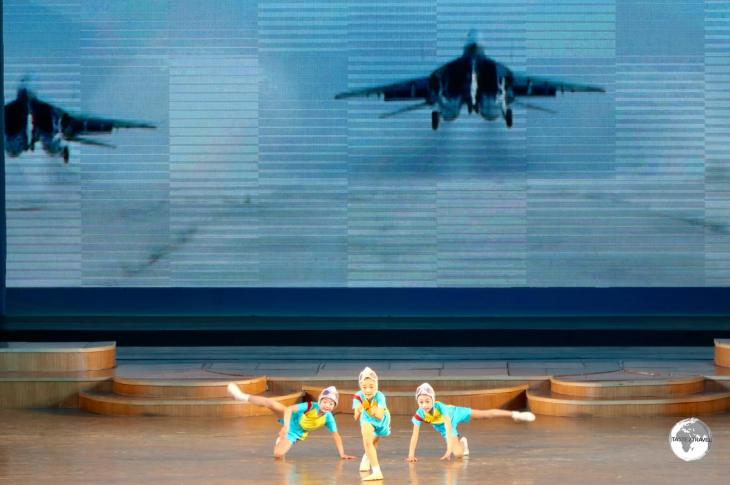 Girls at the Mangyongdae Schoolchildren's Palace in Pyongyang, performing a choreographed <i>flight</i> routine in front of a screen displaying North Korean fighter jets.