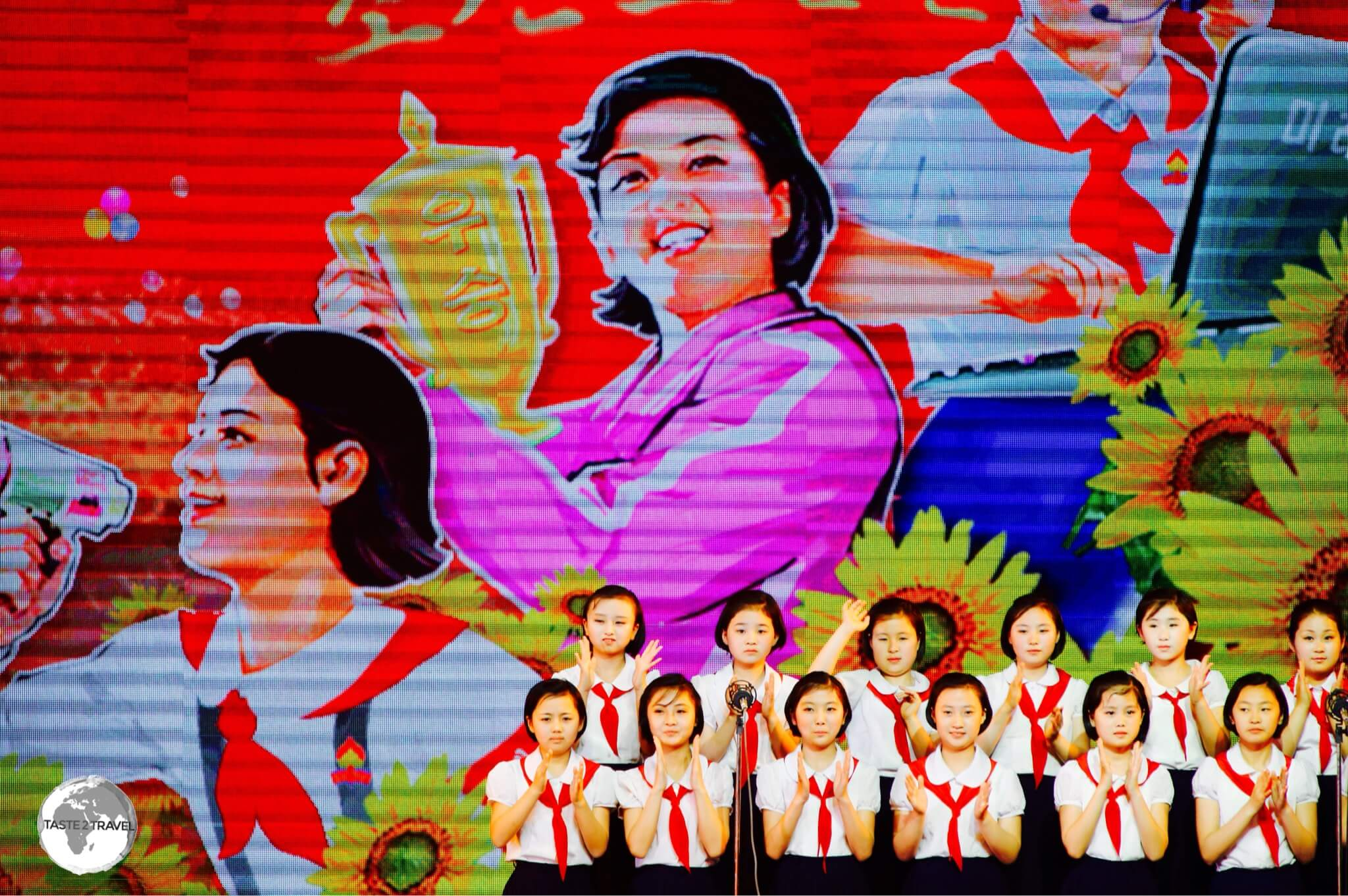 A girls choir performs in front of a propaganda poster.