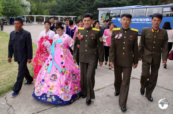 North Korean newlyweds on their way to pay their respects at a statue of the dear leader.