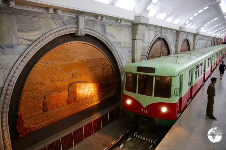 The lights of a train at Puhung Station (terminus of the Chollima line) illuminates one of the large bronze decorative panels.
