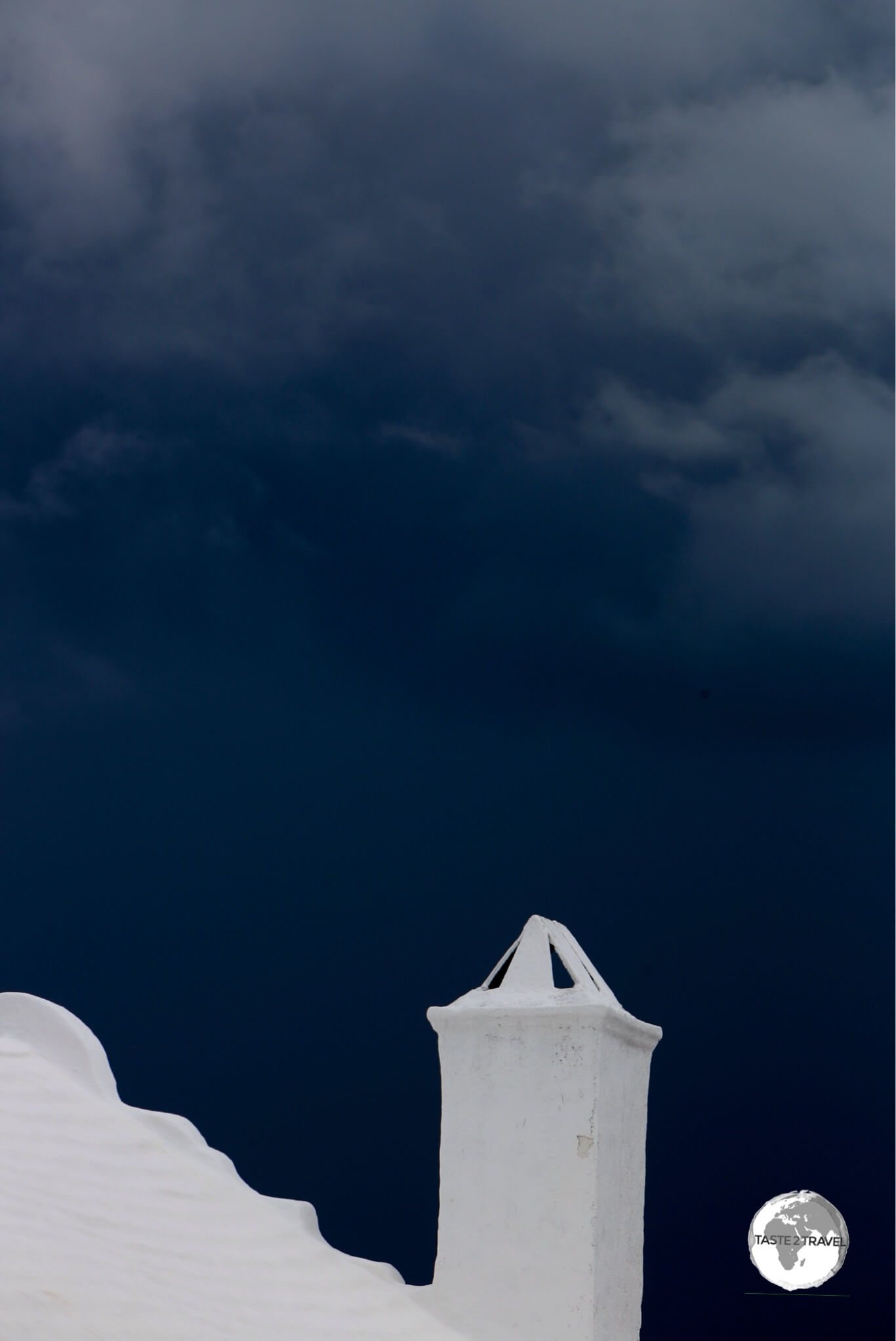 A white-painted, stone roof contrasts starkly against a stormy sky.