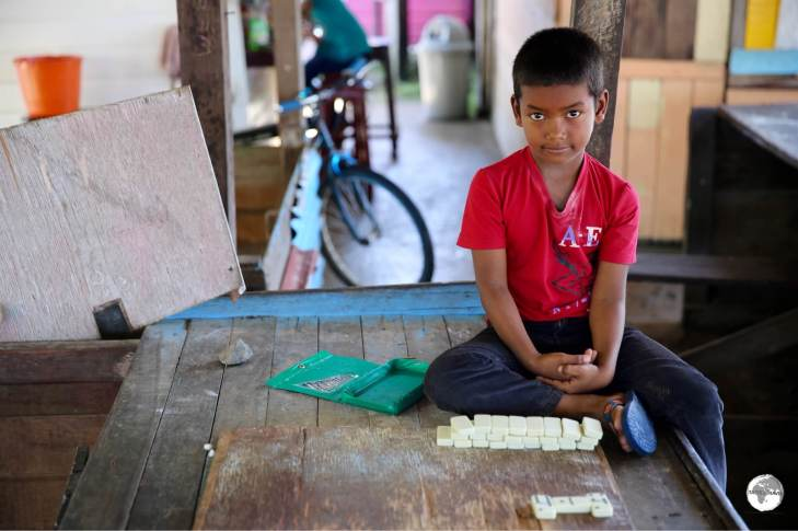 Young boy at the dock in Charity playing dominoes.