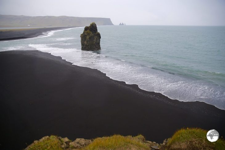 "Arnardrangur or ""Eagle Rock"" stands sentinel on the very black Reynisfjara beach."