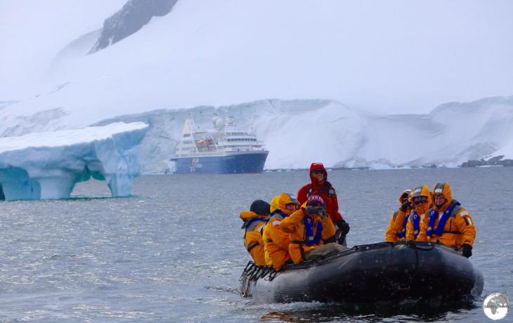 Zodiac cruising around Damoy point with the Ocean Diamond moored in the Neumayer Channel.