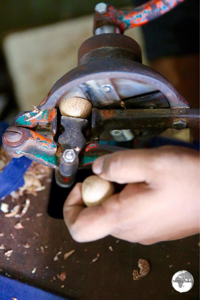Areca nuts being sliced by hand.