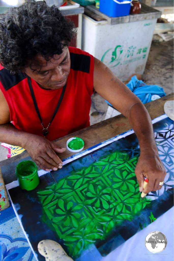 A craftsmen hand-painting a bed sheet.