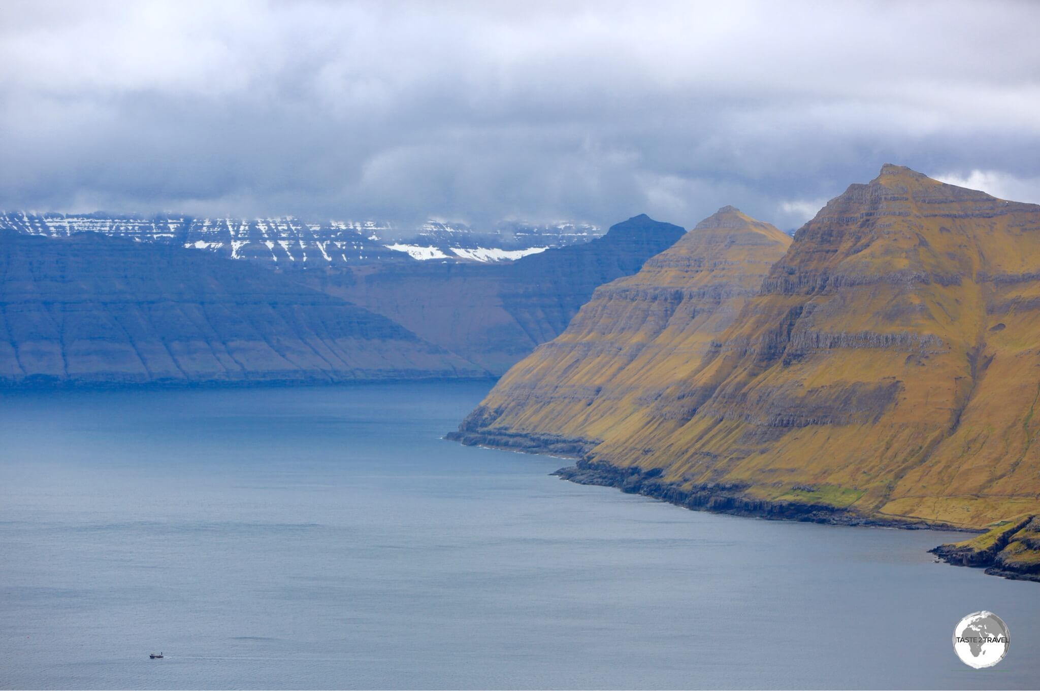 A boat (bottom left) is dwarfed by the towering peaks which surround the Funnings Fjord on Eysturoy Island.