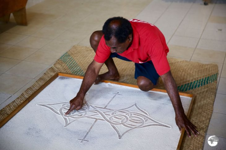 Edgar Hinge of the National Museum of Vanuatu, telling a story using the ancient art of Sand-drawing.