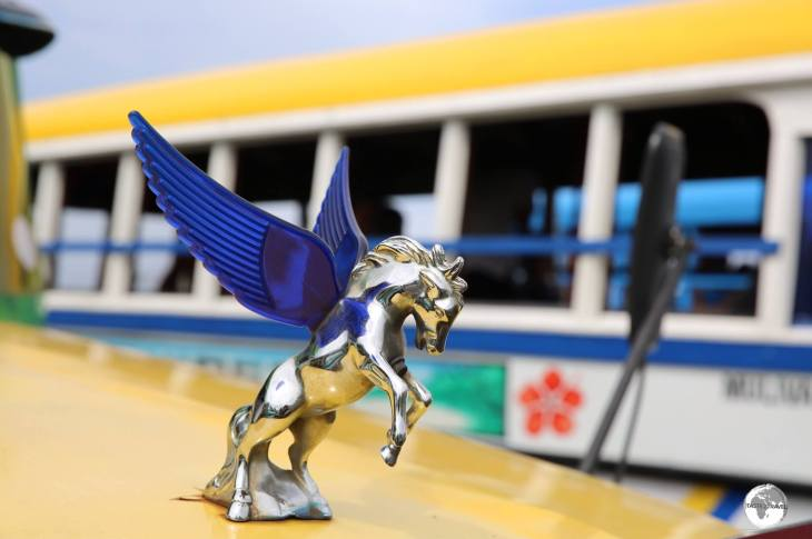A shiny hood ornament on a Samoan bus.