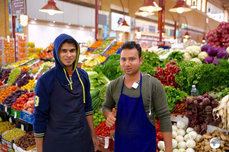 Guest workers constitute 70% of the population and can be found working everywhere, including at the local produce market.
