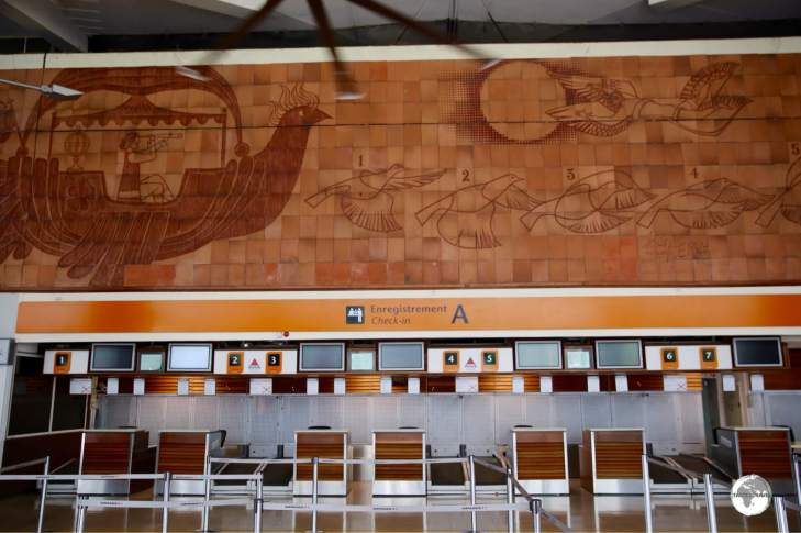 A giant terracotta mural adorns the departure hall at Roland Garros International Airport.