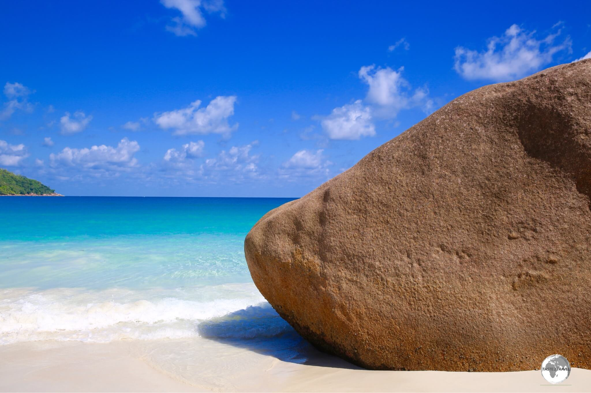 The many terracotta-coloured, granite boulders provide a stark contrast against the turquoise waters and blue skies of the Seychelles.