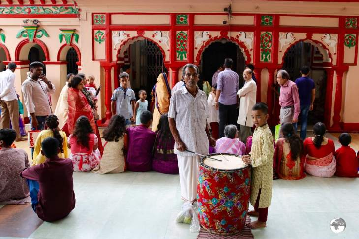 A drummer in front of the main temple at Dhakeshwari Temple.