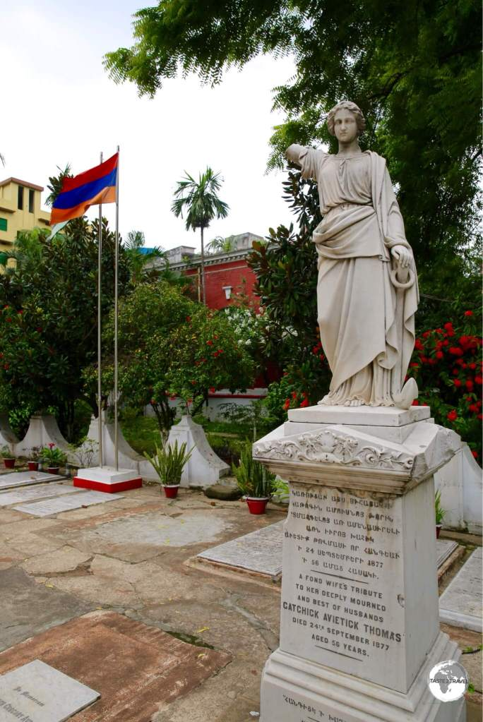 A statue on a gravestone with the Armenian flag in the background.