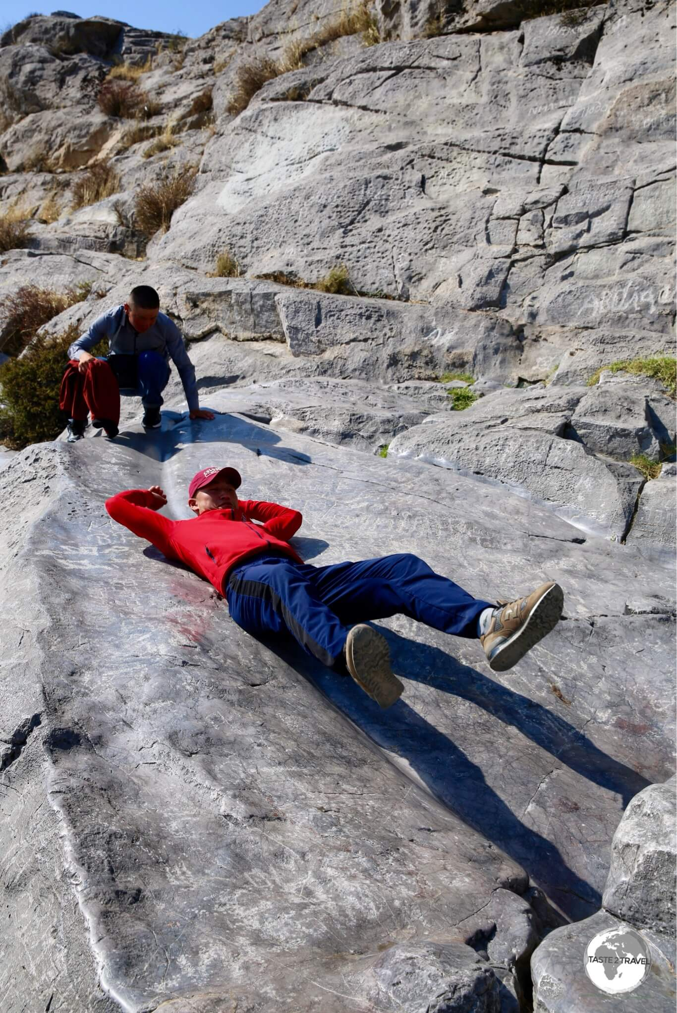Locals sliding down the polished limestone rock on Sulaiman-Too.