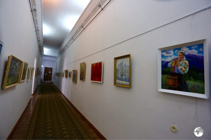 A hallway at the museum is lined with paintings from local artists.