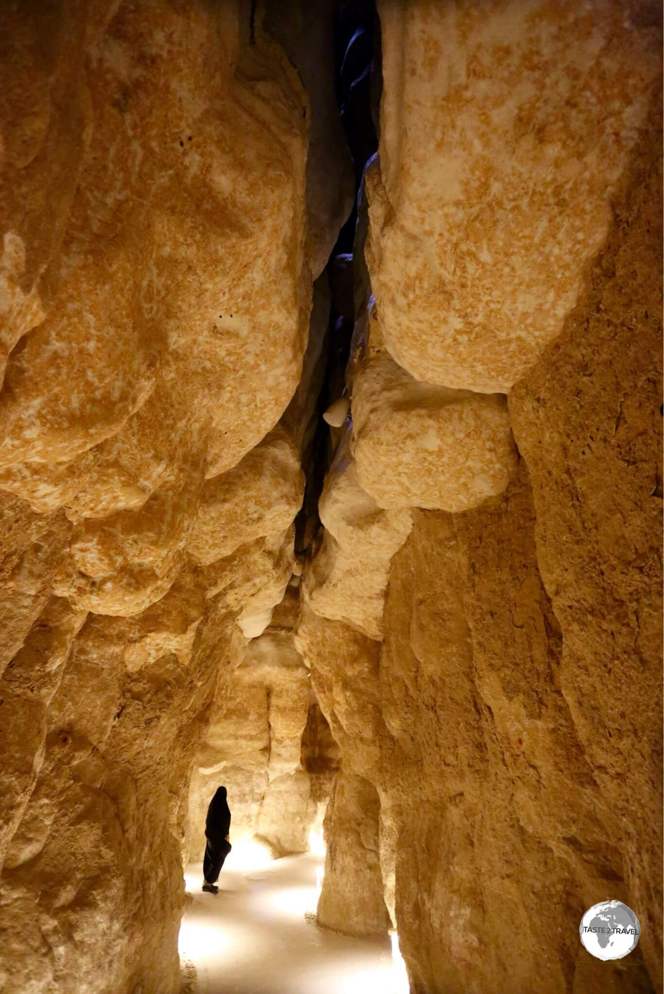 A visitor inside one of the cavities of Al Qarah Mountain.