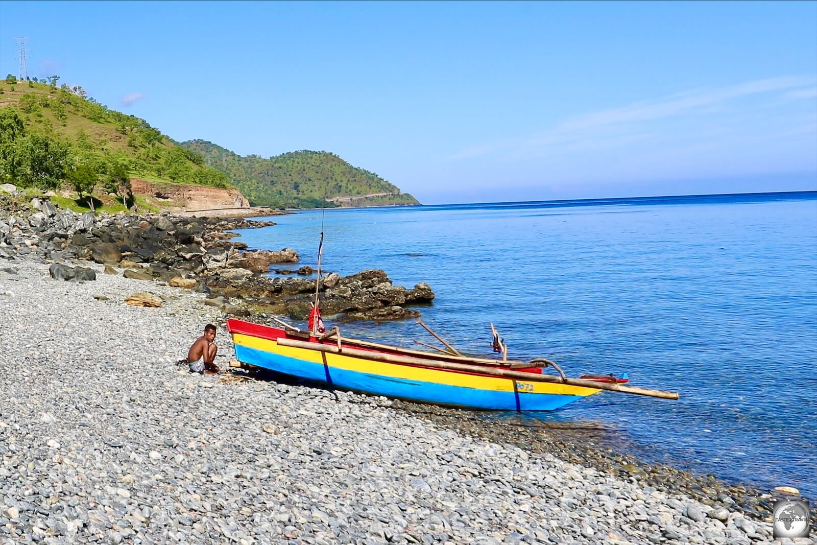 A colourful, traditional, wooden fishing boat on a beach east of Dili.
