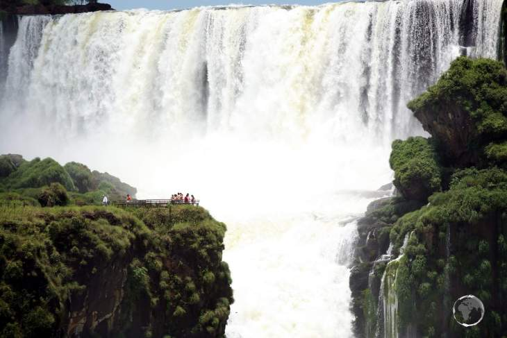 Looking towards the thundering Devils Throat at Iguazú Falls, with tourists visible on the Brazilian side of the falls.