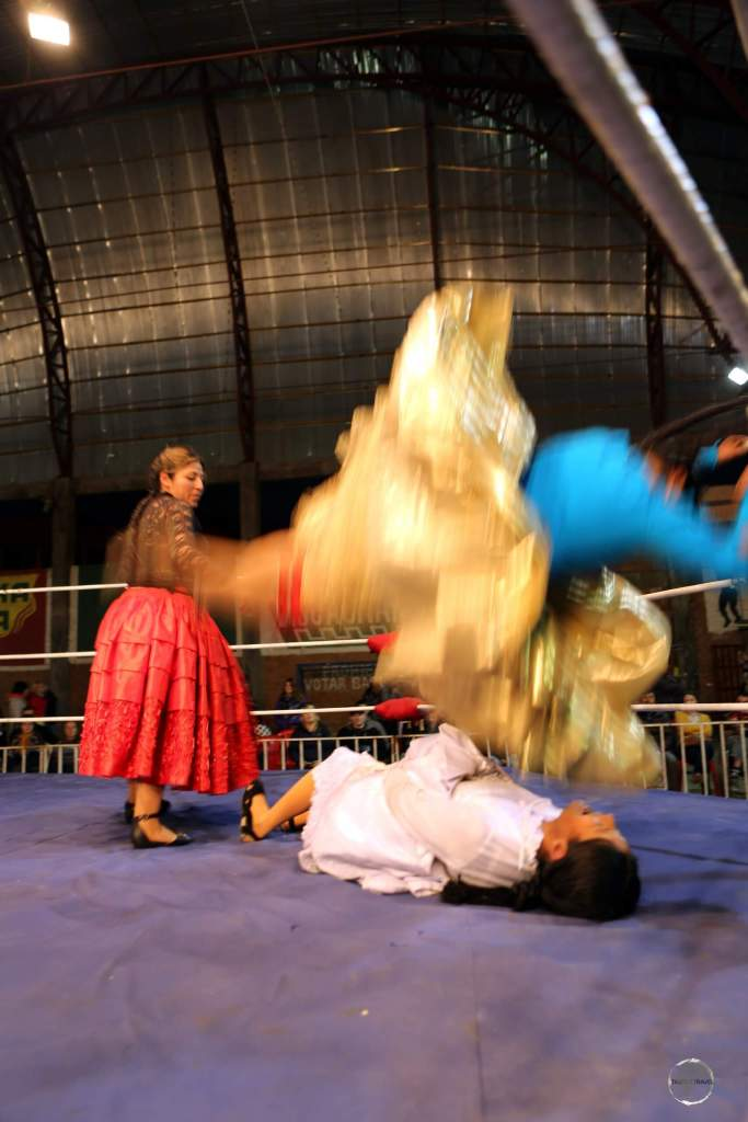 A golden swirl from the outer, plated skirt (la pollera) of an airborne Cholita, as she performs a body slam.