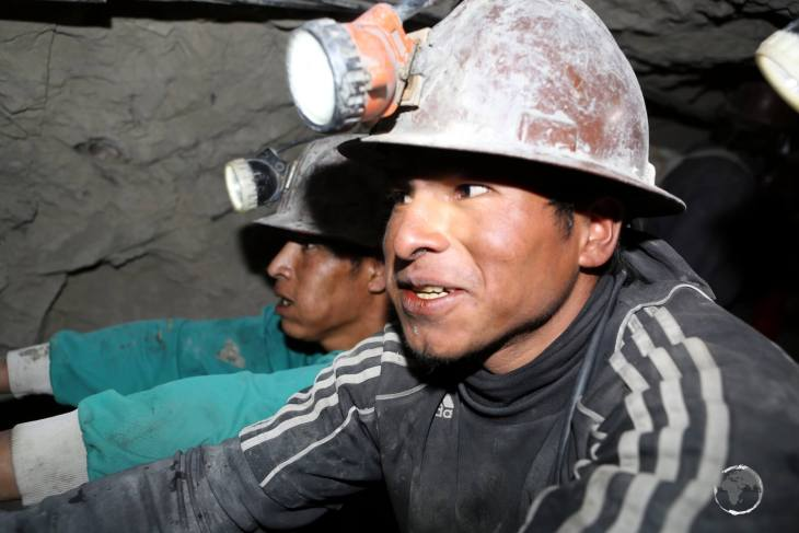 Deep inside Cerro Rico, miners, chewing coco leaves, push past our tour group with a fully loaded wagon of ore. It's claimed that the coca leaves help filter dust.