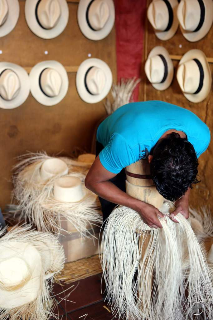 Weaving a Panama hat is back breaking work, requiring the weaver to hold the hat in place using a wood form and their own weight, while they slowly weave down the sides of the hat.