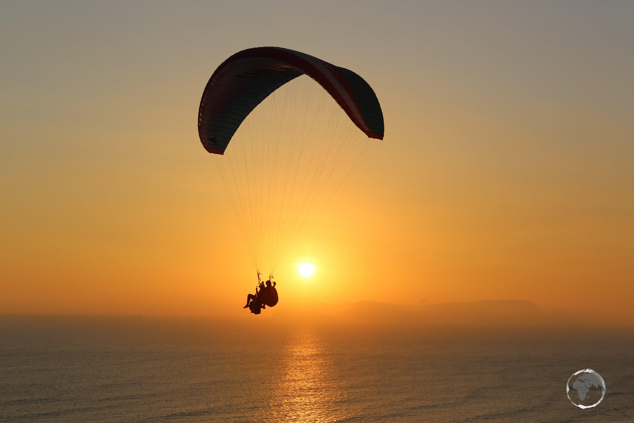 Tandem paragliders taking in the sunset over the Pacific Ocean in Lima, the capital of Peru.