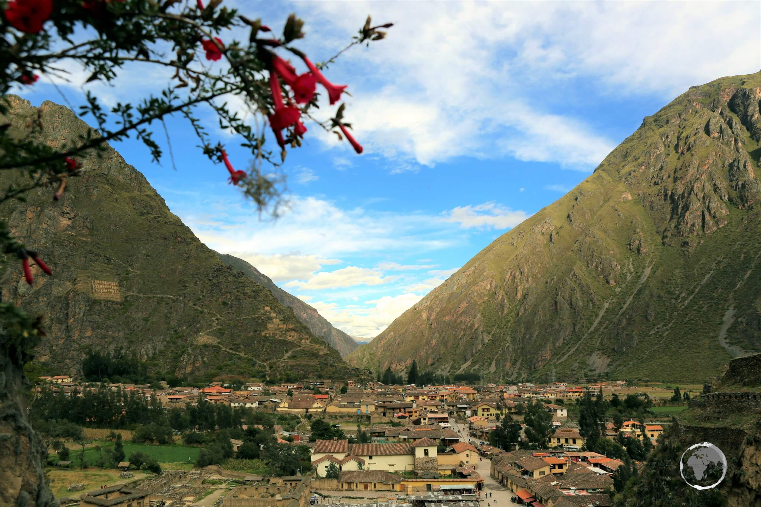 A view of the Peruvian Andean town of Ollantaytambo, from the Ollantaytambo ruins, a massive Inca fortress with large stone terraces on a hillside.
