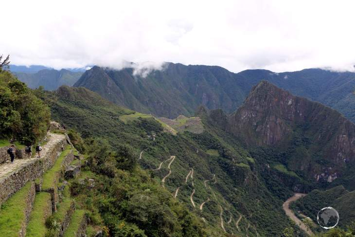 A view from the Inca trail, high in the Peruvian Andes, of a very distant Machu Picchu and the access road winding its way up the mountain from the Urubamba River.