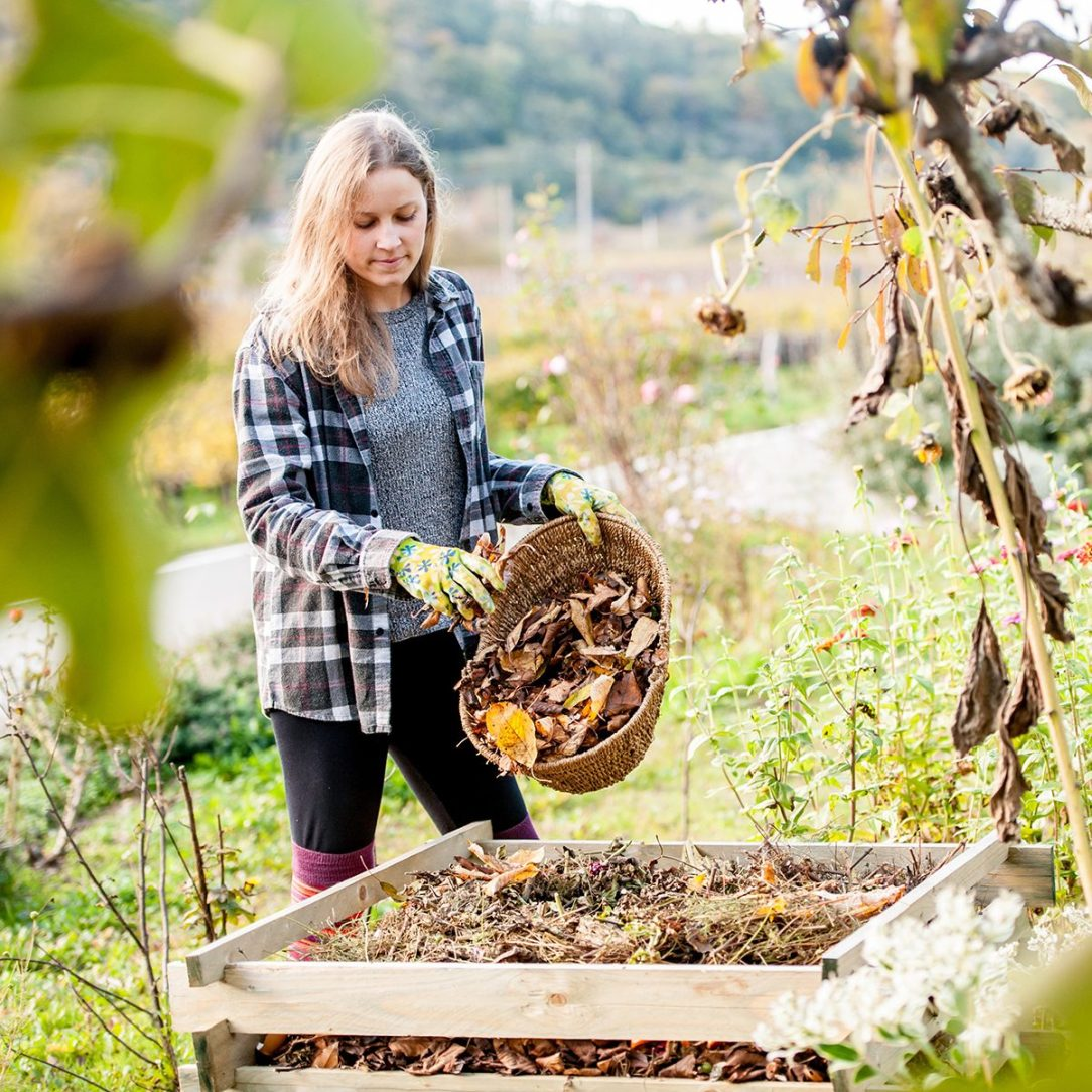 Smiling Young Woman Putting Leaves on Compost.