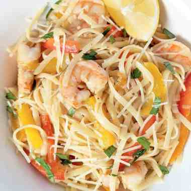 White bowl of linguine pasta with sautéed shrimp, yellow peppers, orange peppers, red peppers, onion, parsley, shredded parmesan cheese, and lemon wedge