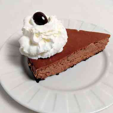 Mexican mocha chocolate crust cheesecake topped with whipped cream and a chocolate covered espresso bean on a white plate