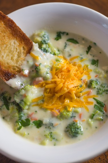 White bowl of broccoli cheddar soup topped with shredded sharp cheddar cheese and chopped parsley served with a piece of crusty buttered bread