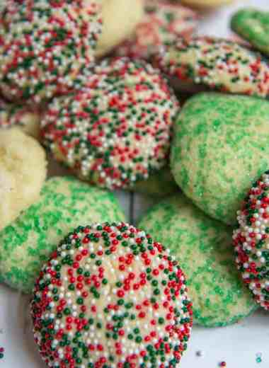 Pile of baked sugar cookies with green, red and white sprinkles sitting on top of white wood backdrop