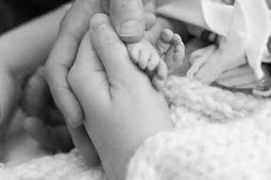 baby feet in parents hands black and white