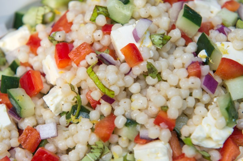 israeli cous cous salad with red pepper, cucumber, feta, red onion, basil and a lemon vinaigrette in a white serving bowl