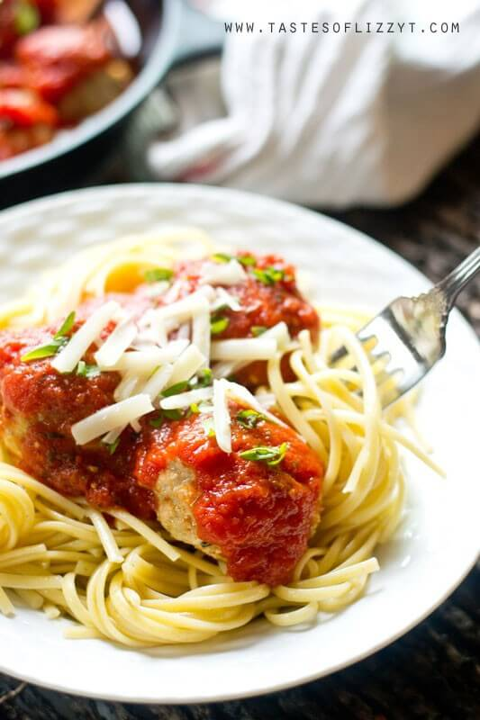 chicken Parmesan meatballs served on a white plate over a bed of cooked spaghetti