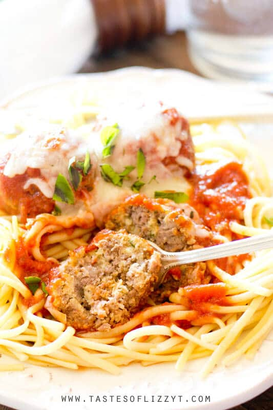 authentic Italian meatballs over pasta. One of the meatballs has been cut in half with a fork