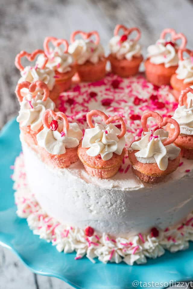 Serve your loved ones this easy-to-decorate strawberry valentine cake. Vanilla buttercream frosted strawberry cake with mini cupcakes, pink candy hearts and sprinkles.