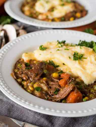 Slow Cooker Shepherd's Pie is an easy way to enjoy a classic casserole. Fork-tender roast beef simmered with veggies & topped with cheesy mashed potatoes.
