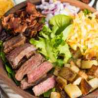 Love steak and potatoes? Try this easy Steak and Potato Salad. Oven fried potatoes, tender steak, cheese, onion and bacon all on top of a bed of spring lettuce. Don't forget the simple 2-ingredient dressing!