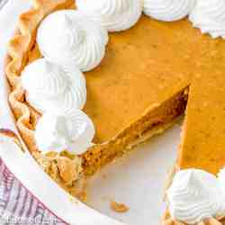 homemade pumpkin pie recipe with a slice taken out of the pie